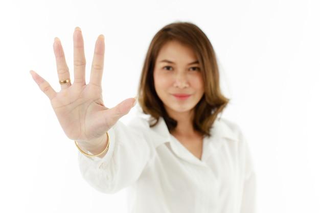 Portret van een aziatische vrouw die zijn vijf vingers laat zien voor nummer 5 of verbieden, weigeren selectieve focus aan kant.