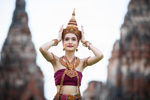 Portret van een aziatische vrouw in thaise traditionele danser kleren staan tegen oude boeddhabeeld. ayuttaya historisch park, thailand azië.