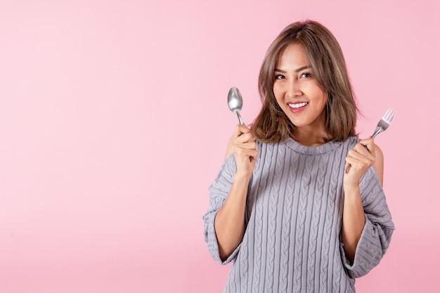 Portret van een aziatische vrouw met een lepel en een vork in zijn hand