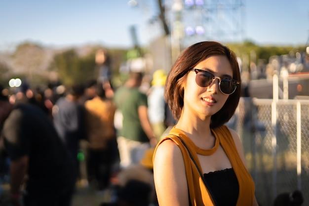 Portret van een aziatische vrouw met een zwarte zonnebril die voor het podium staat op het muziekfestival
