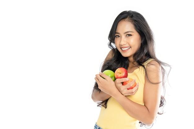 Portret van een aziatische vrouw met veel groene en rode appels