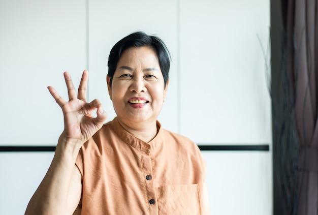 Portret van een aziatische vrouw van middelbare leeftijd die lacht en thuis een goed teken laat zien, het concept van de zorgverzekering