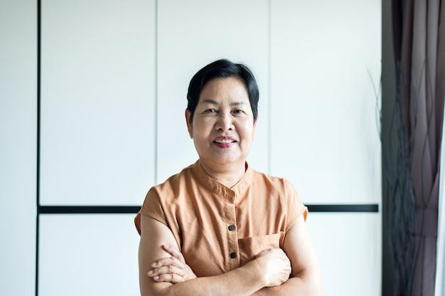 Portret van een aziatische vrouw van middelbare leeftijd die thuis lacht, concept van de zorgverzekering