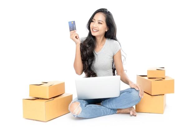 Portret van een aziatische vrouw zittend op de vloer met veel dozen ernaast.