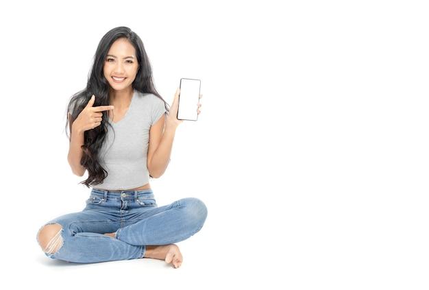 Portret van een aziatische vrouw, zittend op de vloer. ze wees met haar vinger naar de smartphone in haar hand.