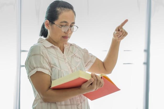 Portret van een aziatische vrouwelijke leraar in wit of schoolbord, die online les geeft met behulp van camera, internet en verlichting