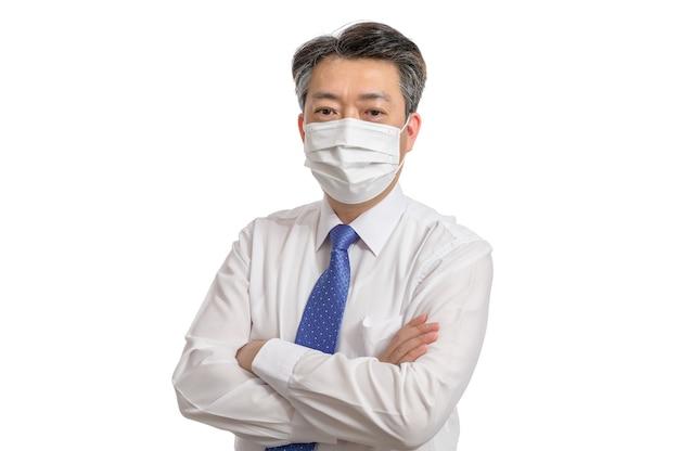 Portret van een aziatische zakenman op middelbare leeftijd die een wit gezichtsmasker draagt.