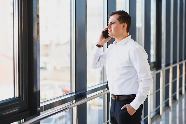 Portret van een baas van een serieuze zelfverzekerde man met een gsm-gesprek tijdens het rusten na een ontmoeting met zijn partners, zakenman praten op mobiele telefoon terwijl staande in de moderne ruimte binnenshuis