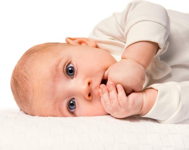 Portret van een baby die in bed thuis ligt.