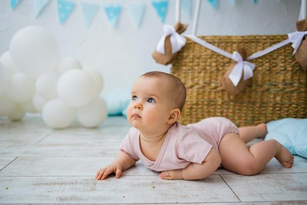 Portret van een baby die op de vloer kruipt tegen de achtergrond van een rieten mand met ballons met ruimte voor tekst