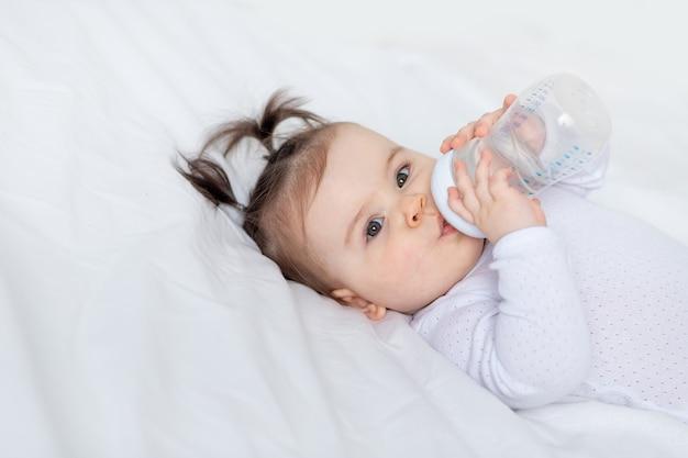 Portret van een baby met een fles op het bed thuis, babyvoedingconcept