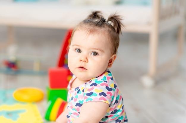 Portret van een baby met speelgoed thuis of in de kleuterschool
