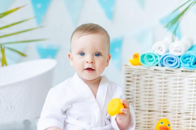 Portret van een babyjongen die na het baden in het bad zit in een wit gewaad met een rubberen eend en een handdoek, het concept van hygiëne en wassen.