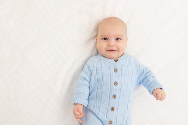 Portret van een babyjongen op het bed. gelukkig lachende baby