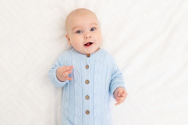 Portret van een babyjongen op het bed. gelukkige glimlachende baby
