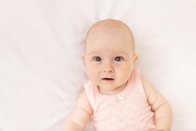 Portret van een babymeisje in een wieg in een roze bodysuit zes maanden op een wit katoenen bed