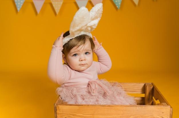 Portret van een babymeisje met hazenoren, zittend in een houten doos met kleurrijke eieren op een gele achtergrond