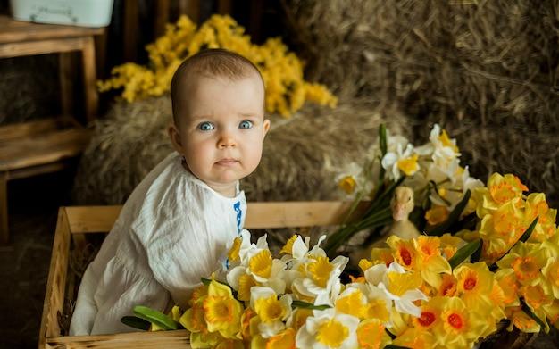 Portret van een babymeisje, zittend in een houten kar met gele bloemen en een gele eend