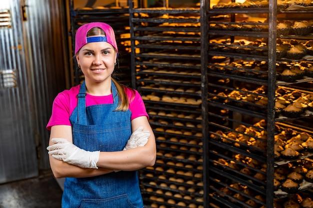 Portret van een bakkersmeisje tegen de achtergrond van planken met vers brood in een bakkerij. industriële broodproductie