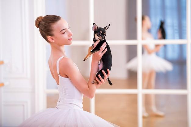 Portret van een ballerina in het wit met een kleine chihuahuahond in haar handen in een mooie witte kamer voor een spiegel.