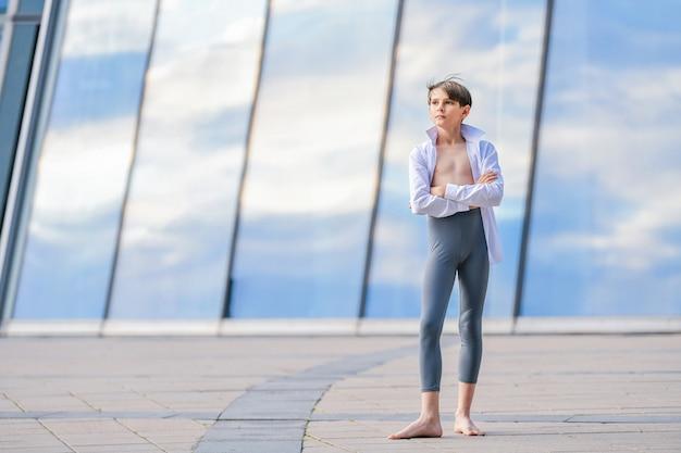 Portret van een balletjongen die traint tegen een achtergrond van luchtreflectie in glazen wand