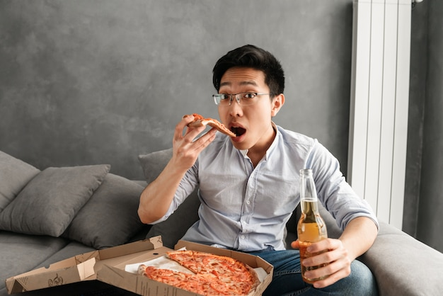 Portret van een bang jonge aziatische man pizza eten