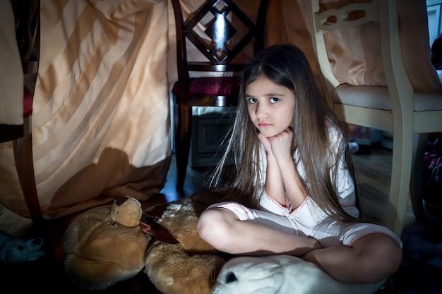 Portret van een bang klein meisje dat op een griezelige donkere nacht op de vloer zit