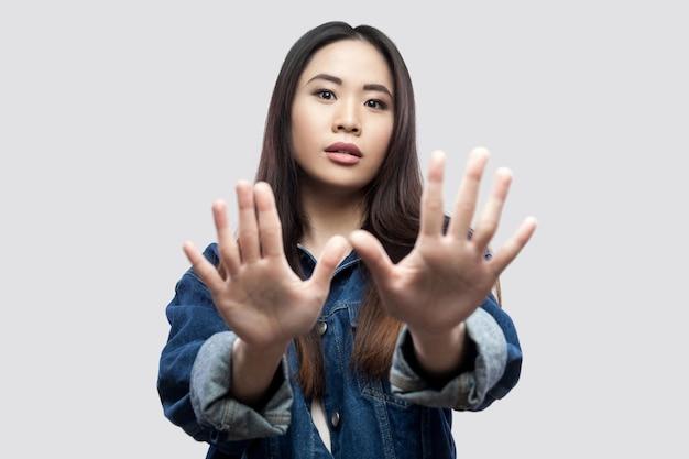 Portret van een bang mooie brunette aziatische jonge vrouw in een casual blauw spijkerjasje met make-up die met de hand blokkeert en naar de camera kijkt. indoor studio-opname, geïsoleerd op lichtgrijze achtergrond