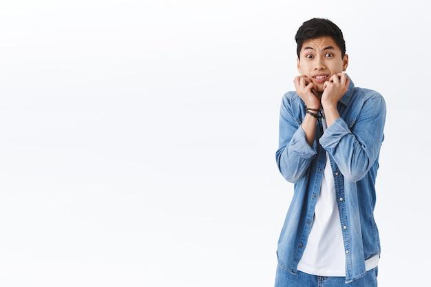Portret van een bange jonge timide aziatische man die een griezelige persoon ziet, bevende angst, handen tegen elkaar drukken en bang staren, bang zijn voor horrorfilm, staande doodsbange witte muur