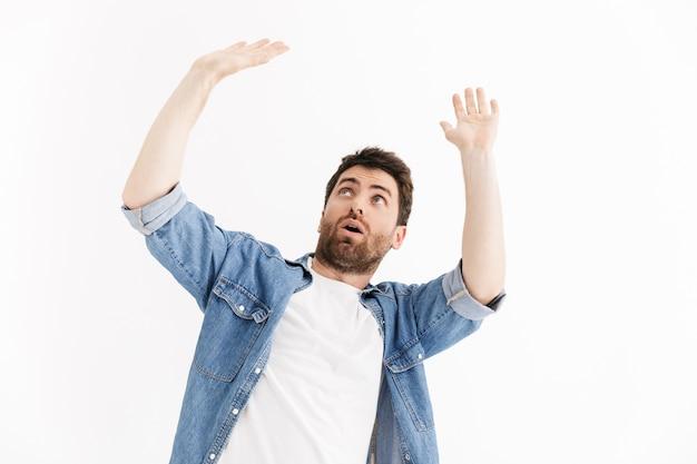 Portret van een bange knappe bebaarde man die casual kleding draagt die geïsoleerd staat, bedekt zichzelf met handen