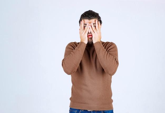 Portret van een bange man die zijn gezicht bedekt met handpalmen en door geïsoleerde vingers kijkt