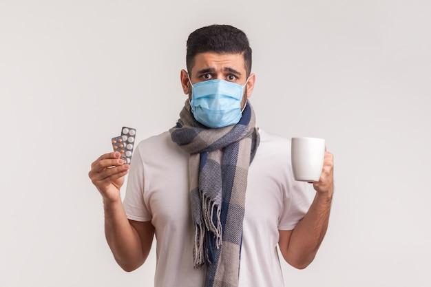 Portret van een bange man met een beschermend hygiënisch masker met pillen en een kopje thee, wanhopig op zoek