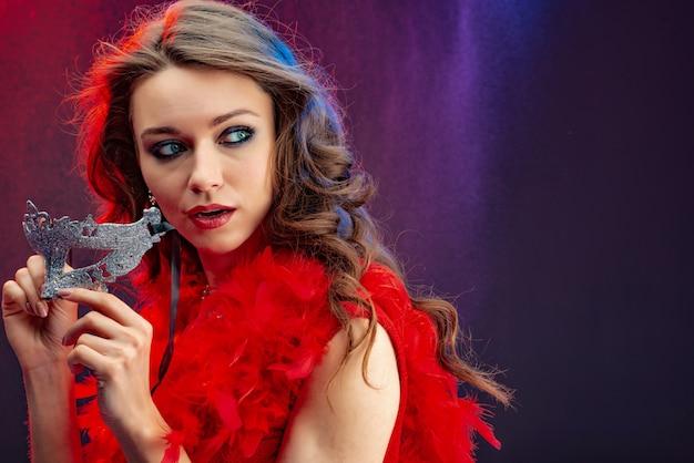 Portret van een bange vrouw met carnaval masker in haar handen