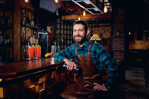 Portret van een barman hipster met baard glimlachend zittend in staaf