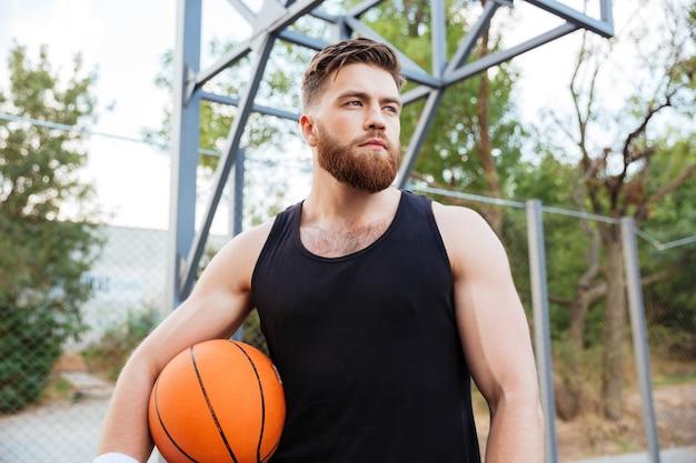 Portret van een bebaarde basketballer die buiten met een bal staat