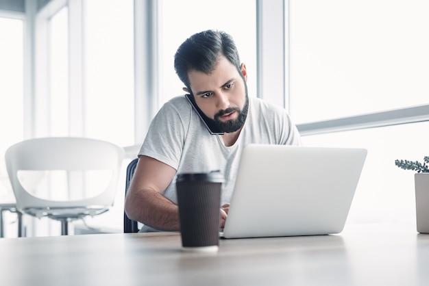 Portret van een bebaarde donkerharige man die in een wit kantoor zit en naar zijn laptopscherm kijkt terwijl hij aan het telefoneren is. zijn kopje koffie staat voor hem