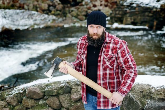 Portret van een bebaarde houtvester in de winter in het bos