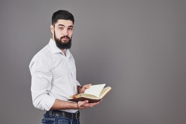 Portret van een bebaarde jonge man die een wit overhemd draagt en een open planner en een pen vasthoudt. een grijze muurachtergrond.