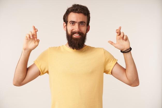 Portret van een bebaarde jonge man met een geel t-shirt in een casual stijl met gekruiste vingers staand
