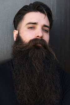 Portret van een bebaarde jonge man tegen een grijze achtergrond