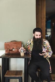 Portret van een bebaarde jonge man zit in café met behulp van de mobiele telefoon
