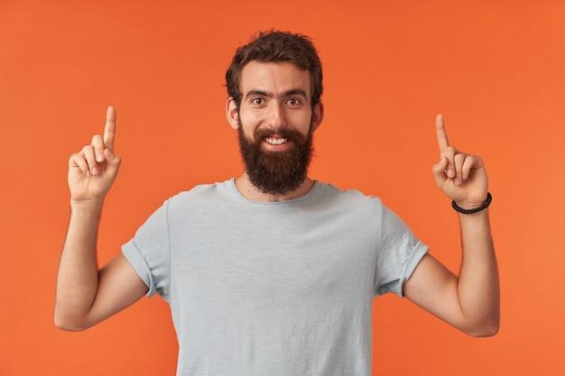 Portret van een bebaarde jongeman met bruine ogen in wit t-shirt wijst met de vingers omhoog, kijkt naar jou en omhoog emotie gelukkig blij en zelfverzekerd staan