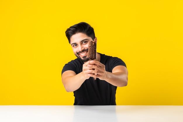 Portret van een bebaarde knappe indiase jonge man die ijs eet in kegel of ijslolly terwijl hij aan tafel zit tegen een gele studioachtergrond