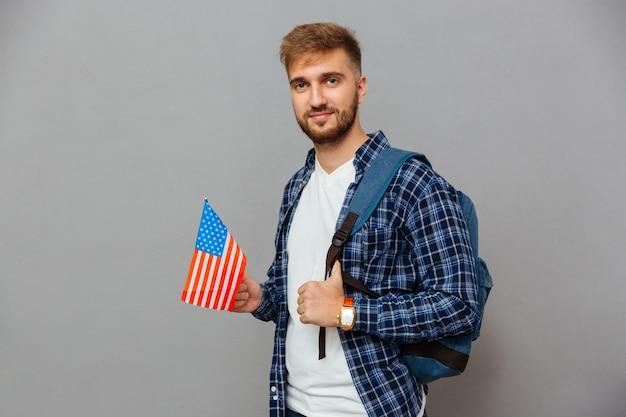 Portret van een bebaarde man die met een rugzak staat en de vlag van de v.s. geïsoleerd op een grijze muur vasthoudt