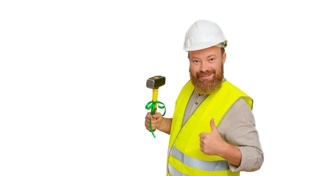Portret van een bebaarde man, een bouwer in een witte helm en een geel vest met een hamer in zijn hand