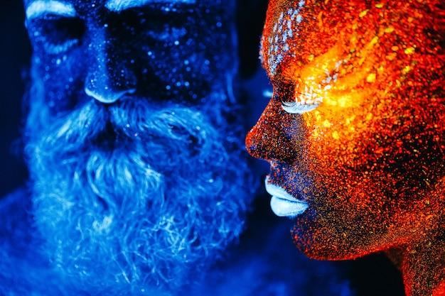 Portret van een bebaarde man en vrouw geschilderd in ultraviolet poeder.