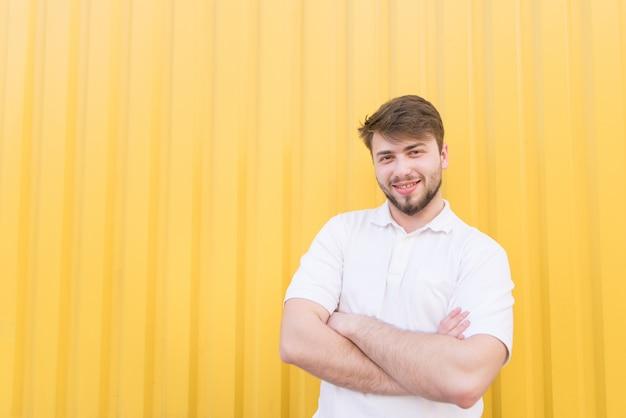 Portret van een bebaarde man gekleed in een wit t-shirt op een gele muur.