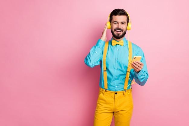 Portret van een bebaarde man houdt gsm luisteren muziek in oortelefoons