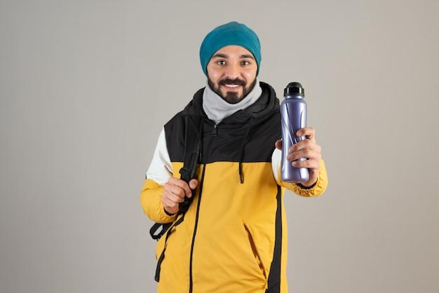 Portret van een bebaarde man in een warme muts die een waterfles vasthoudt tegen een grijze muur.