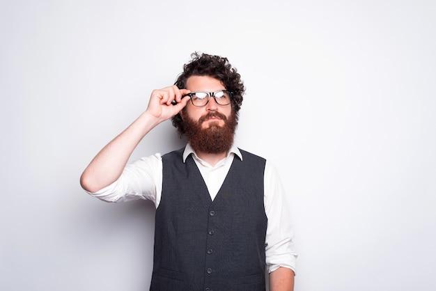 Portret van een bebaarde man in pak brillen aan te raken en serieus weg te kijken